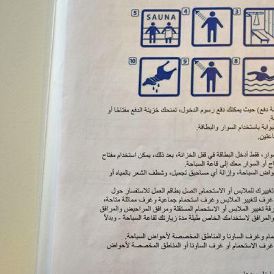 Vieraskieliset ohjeet uimahallissa kävijälle.