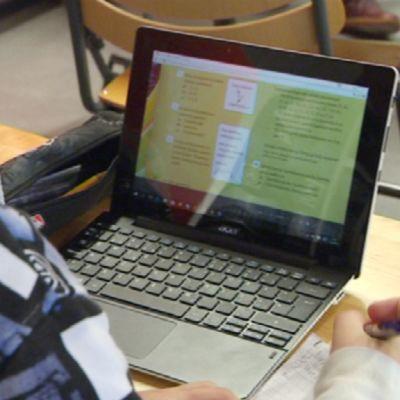 Koululainen opiskelee kannettavan tietokoneen avulla.