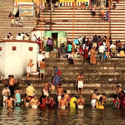 Ihmiset kylpevät Gagnesissa, Varanasin kaupungissa.  Ihmisiä on myös taustalla näkyvilla portailla.