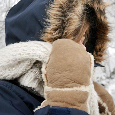 Talvivaatteisiin pukeutunut nainen lumisessa maisemassa.
