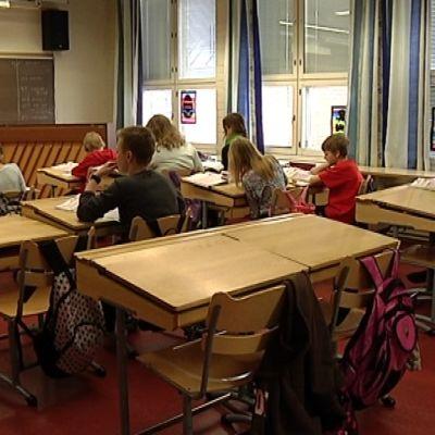 Ala-asteen oppilaita tunnilla pulpeteissa.