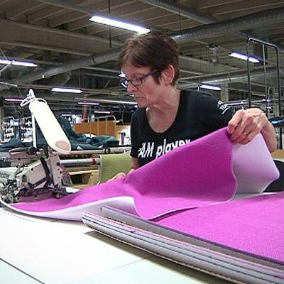 Työntekijä ompelee tyynynpäällistä Lennolin tehtaalla.