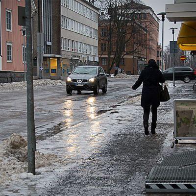Katunäkymä Kokkolasta jalankulija kävelee, auton valot kiiltävät jäisellä kadulla.
