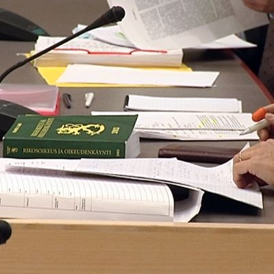 Mies tutkii papereita oikeudessa.