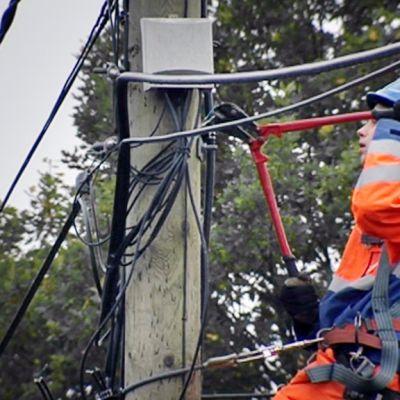 Sähköyhtiön työntekijä korjaa ilmassa roikkuvaa sähköjohtoa.