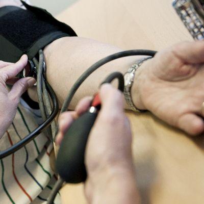 Naisen verenpainetta mitataan lääkärin vastaanotolla.