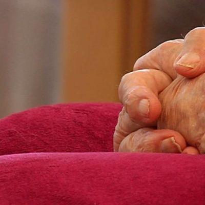 Vanhuksen kädet ristissä.