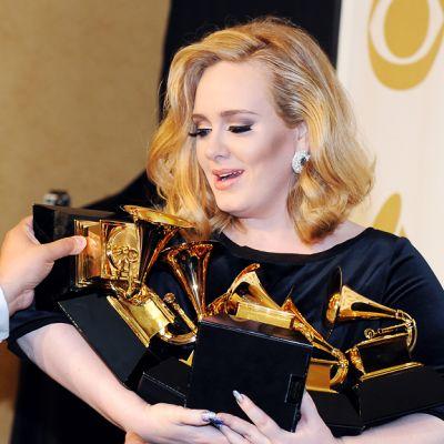 Avustaja asettelee Grammy-palkintoja Adelen syliin.