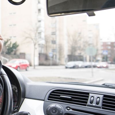 Henkilöauton kuljettaja näyttää keskisormea tiellä kulkevalle.