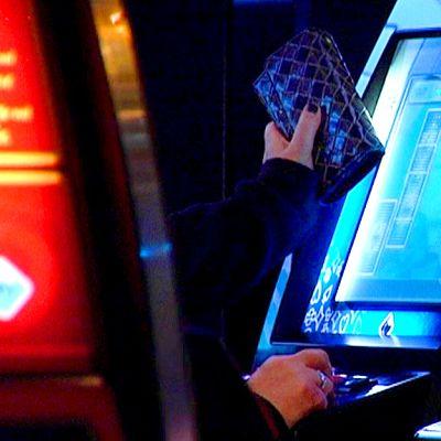 Nainen pelaa rahapeliä.