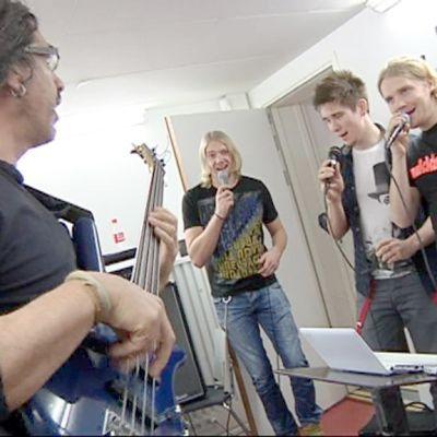 Kolme poikaa laulamassa, musiikinopettaja säestää kitaralla.