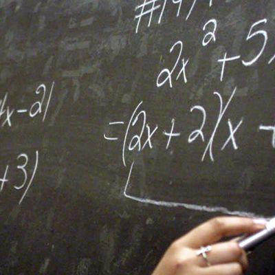 Opettaja kirjoittaa laskutoimituksia liitutaululle.