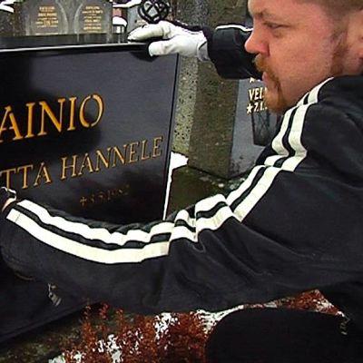 Jere-Miikka Myllymäki puhdistaa hautamuistomerkin asennuksen jälkeen.
