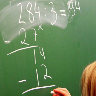 Ala-asteen oppilas laskee matematiikan tehtävää koulun liitutaululla.