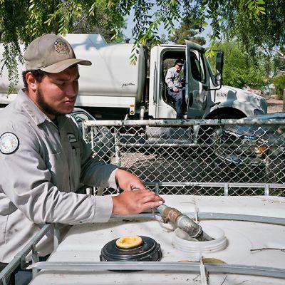 Kunnan työntekijät Christian Manns (etualalla) ja Clyde Loflin (taustalla) täyttävät omakotitalon vesisäiliötä East Portervillessa.