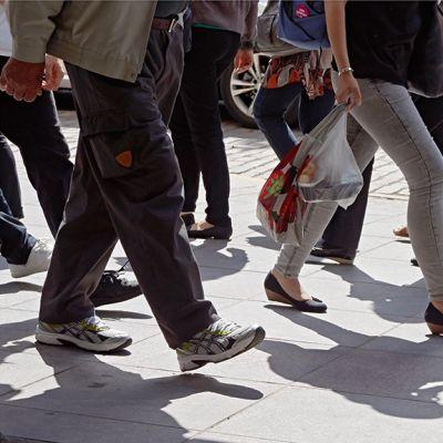 Ihmisten jalkoja kadulla.