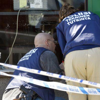 Poliisi tutkii luodinreikiä ravintola Medicin Manin ikkunassa.