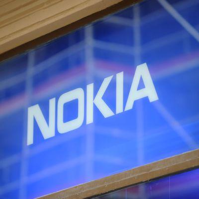 Nokian logo ikkunassa, johon heijastuvat ympäröivien rakennusten telineet.