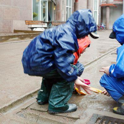 Sadeasuiset lapset leikkivät päiväkodin pihalla.