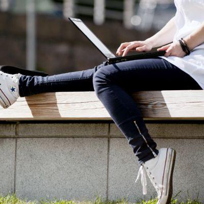 Henkilö käyttää kannettavaa tietokonetta ulkona.
