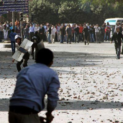 Egyptiläiset mielenosoittajat heittelevät kivillä mellakkapoliiseja Tahririn aukiolla Kairossa.