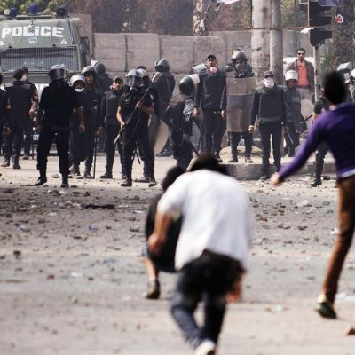 Mielenosoittajat heittelevät poliiseja kivillä kadulla.