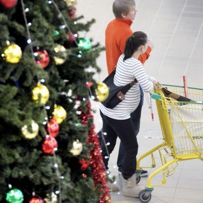 Joulukuusi ja asiakkaita ostoskeskuksessa.