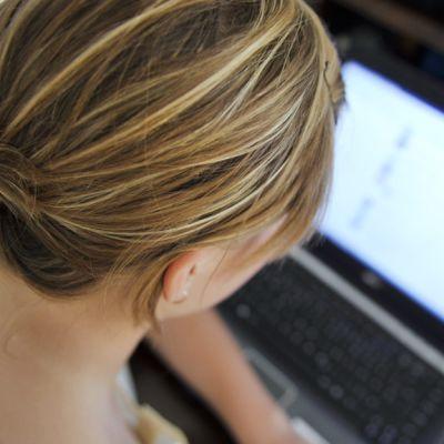 Nuori nainen käyttää tietokonetta.