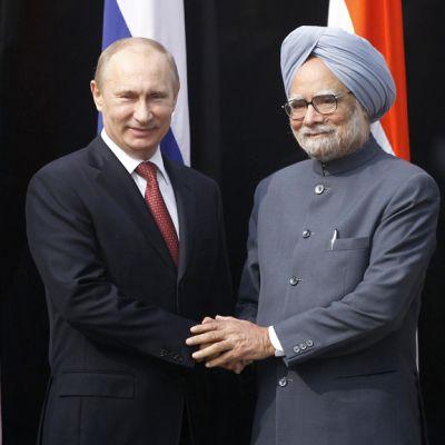 Putin ja Singh kättelevät maiden lippujen edessä.