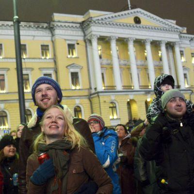 Ihmisiä seuraamassa uudenvuoden ilotulitusta Senaatintorilla.