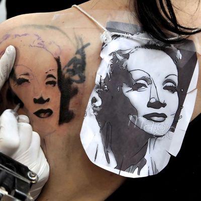 Tatuoija tekee Marlene Dietrichin kuvaa nuoren naisen selkään.