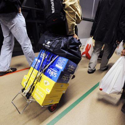 Matkustajat kärräävät olutlaatikoita satamassa.