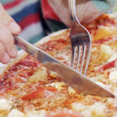 Nainen syö pitsaa.