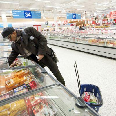 Mies ottaa ruokaa kaupan pakastealtaasta.