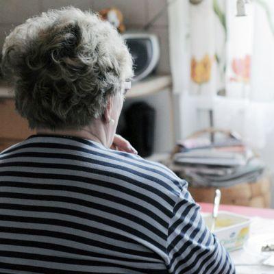 Iäkäs nainen istuu yksin keittiön päydän ääressä kotonaan.