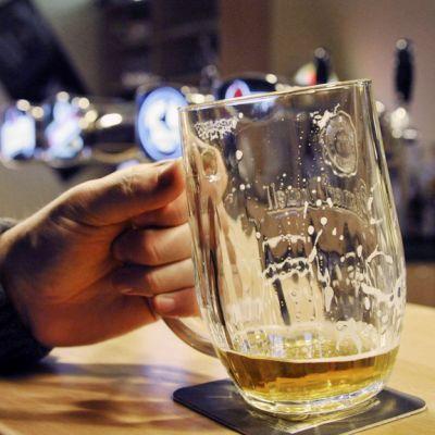 Mies juo olutta ravintolan baaritiskillä.