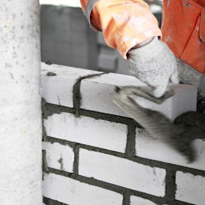 Tiiliseinää muurataan rakennustyömaalla.