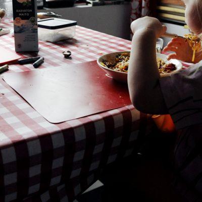 Isä ja lapsi syövät keittiön pöydän ääressä.