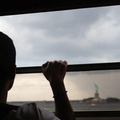 Poika katselee Vapaudenpatsasta lautan ikkunan ääressä New Yorkissa.