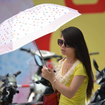 Nainen suojelee itseään paahtavalta auringolta Shanghaissa 4. heinäkuuta 2013.
