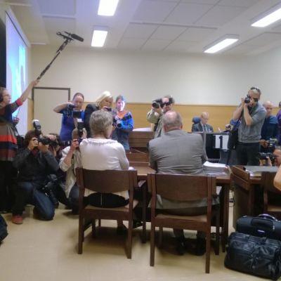 Toimittajat kuvaavat miestä ja naista Satakunnan käräjäoikeudessa. Nainen on Anneli Auer.
