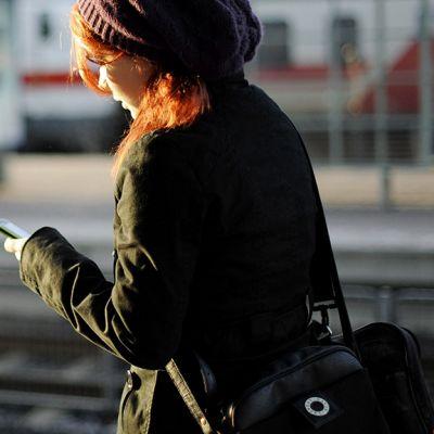 Nuori nainen katsoo puhelintaan juna-aseman laiturilla.