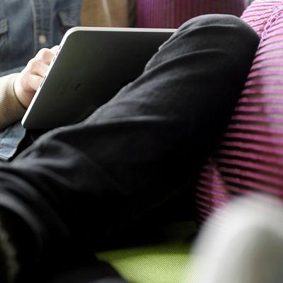 Mies selaa taulutietokonetta sohvalla.