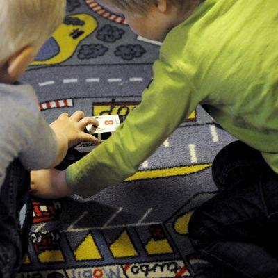 Lapset leikkivät autoilla lattialla.