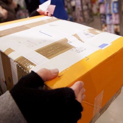 Postipaketti asiakkaan kädessä postissa.