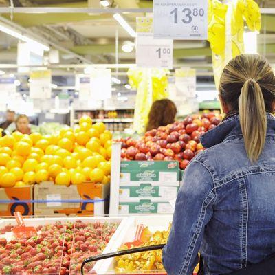 Nainen ruokakaupan vihannestiskillä.