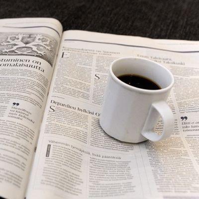 Tabloid-kokoisen Helsingin Sanomien pääkirjoitussivu aamukahvipöydässä Helsingissä 8. tammikuuta 2013.