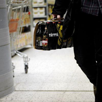 Mies kantaa olutta ruokakaupassa.