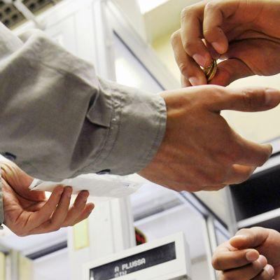 Työntekijä käsittelee rahaa kaupan kassalla.