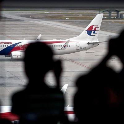 Malesialaiset lapset kuvaavat  Malaysian Airlinesin lentokonetta Kuala Lumpurin kansainvälisellä lentokentällä.